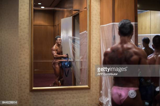 In this photo taken on September 2 a bodybuilder walks backstage prior to competing in the 2017 NABBA WFF Asia Seoul Open Bodybuilding Championship...
