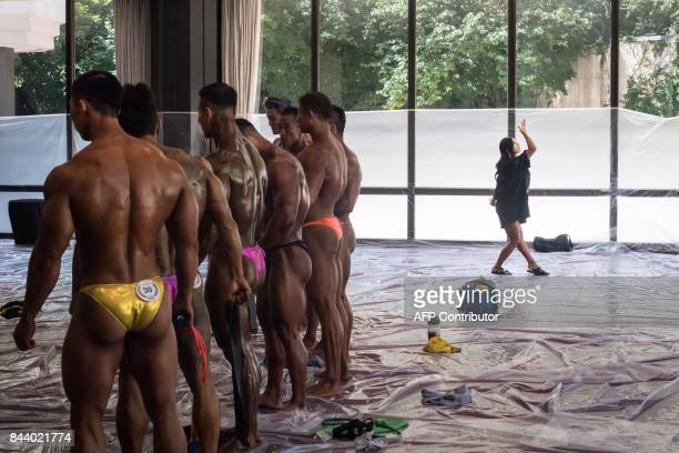 In this photo taken on September 2 a model practices posing backstage prior to competing in the 2017 NABBA WFF Asia Seoul Open Bodybuilding...