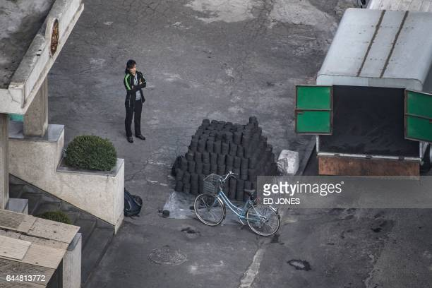 In this photo taken on September 22 a woman stands before a delivery of coal brickettes outside an apartment building in Pyongyang North Korea on...