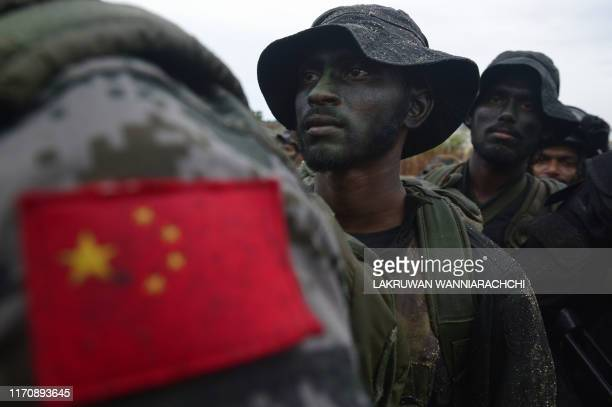 TOPSHOT In this photo taken on September 23 2019 shows a Chinese soldier standing with Sri Lankan military personnel during a training exercise on...