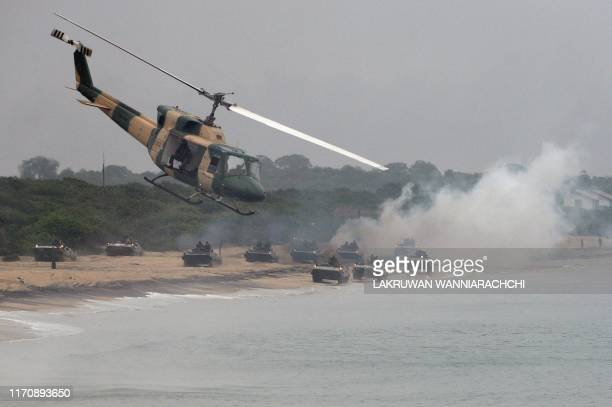 In this photo taken on September 23 2019 shows a helicopter flying past as Sri Lankan military personnel in tanks take in a training exercise on the...