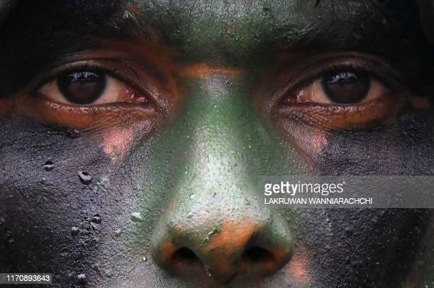 In this photo taken on September 23 2019 shows a Sri Lankan military personnel wearing face paint during a training exercise on the eastern coast of...