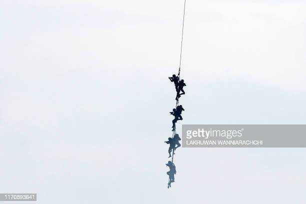 In this photo taken on September 23 2019 shows Sri Lankan military personnel hanging on a rope from a helicopter as they take part in a training...
