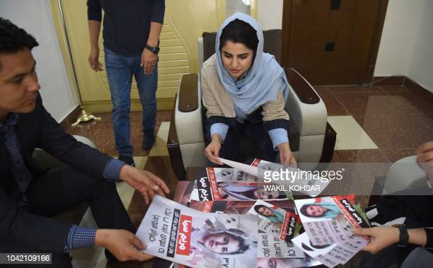 In this photo taken on September 26 Afghan parliamentary election candidate Maryam Sama checks her election campaign posters in Kabul Campaigning for...