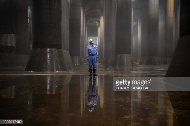 In this photo taken on September 3 an employee stands in the water tank of the metropolitan outer underground discharge channel in Kasukabe, Saitama...