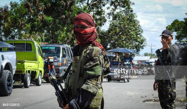 TOPSHOT In this photo taken on September 5 2017 shows a Moro Islamic Liberation Front rebel with face covered along with a government soldier manning...