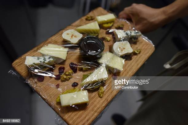 In this photo taken on September 8 a chef puts a cheese platter featuring French brie and other cheeses in a refridgerator at a restaurant in Beijing...