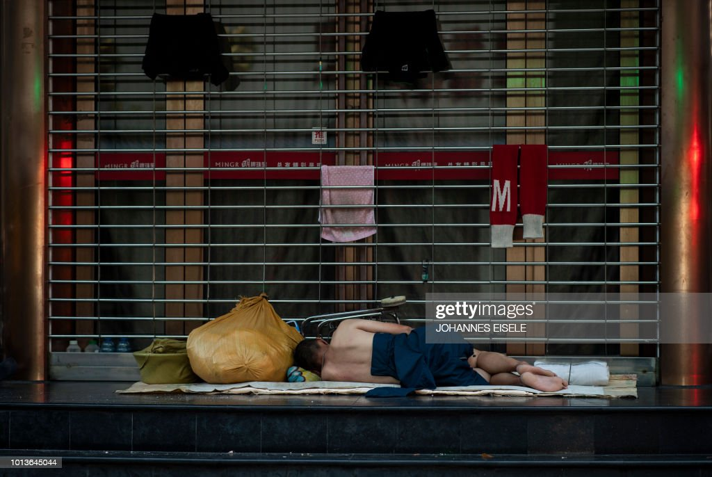 In this photo taken shortly after midnight on August 9, 2018, a man sleeps in front of a shopping mall along Nanjing East Road, a popular pedestrian street filled with shoppers and tourists during the day, to escape the heat of residential apartments in Shanghai. - Normally bustling Nanjing East Road has turned into an open-air slumber party on recent nights as local residents try to beat the heat of their cramped nearby homes by sleeping outside on benches or directly on the pavement. Many homes in some of Shanghai's low-rise older neighbourhoods lack air conditioning, while residents that do have it will often seek ways to keep electricity bills from skyrocketing during summer.