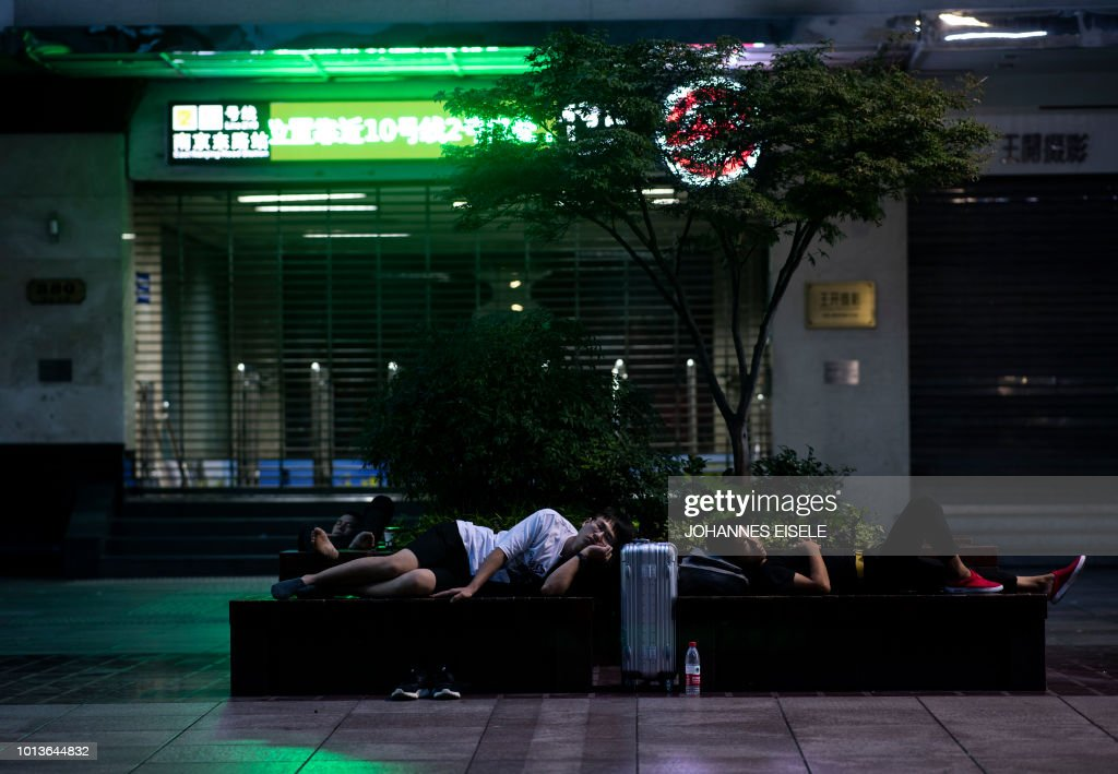 In this photo taken shortly after midnight on August 9, 2018, two men sleep on benches along Nanjing East Road, a popular pedestrian street filled with shoppers and tourists during the day, to escape the heat of residential apartments in Shanghai. - Normally bustling Nanjing East Road has turned into an open-air slumber party on recent nights as local residents try to beat the heat of their cramped nearby homes by sleeping outside on benches or directly on the pavement. Many homes in some of Shanghai's low-rise older neighbourhoods lack air conditioning, while residents that do have it will often seek ways to keep electricity bills from skyrocketing during summer.