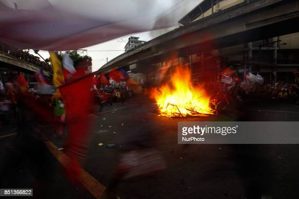 In this photo taken with a slow shutter speed activists run around a burning cubic effigy painted with the face of President Rodrigo Duterte and...