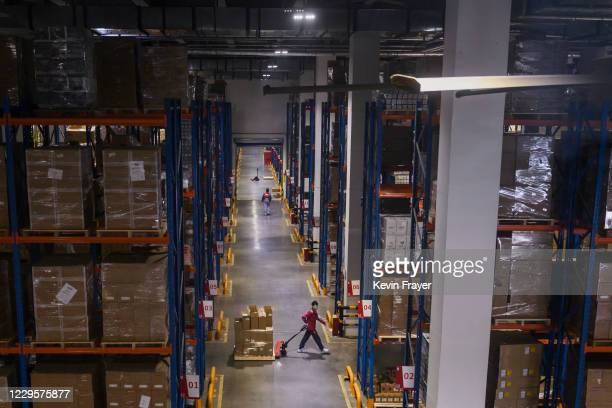 In this photo takent through glass, workers from Chinese e-commerce giant JD.com work in the warehouse at the company's main logistics hub during an...