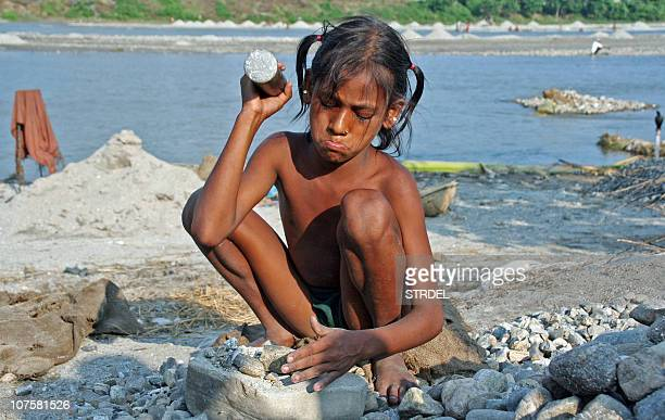 STORY 'INDIACHILDLABOURRIGHTS' In this photograph dated 06 October 2006 Pinky an eleven year old girl breaks stones on the bank of the Balason river...