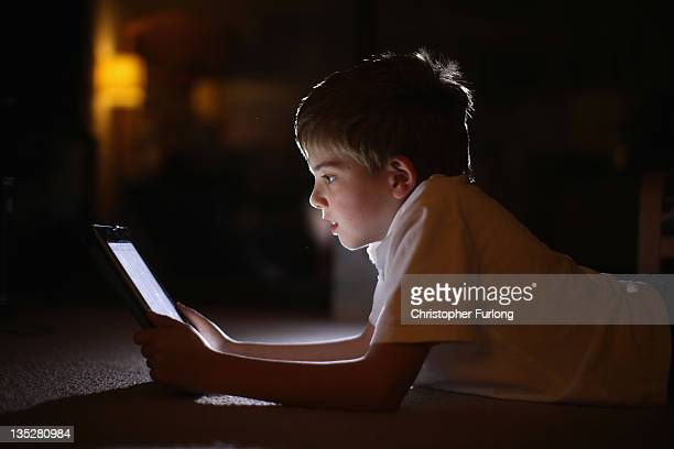 In this photograph illustration a ten-year-old boy uses an Apple Ipad tablet computer on November 29, 2011 in Knutsford, United Kingdom. Tablet...
