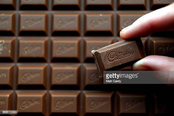 In this photograph illustration a woman picks up a chunk of chocolate from a bar of Cadbury's Dairy Milk chocolate on January 19 2010 in Bristol...