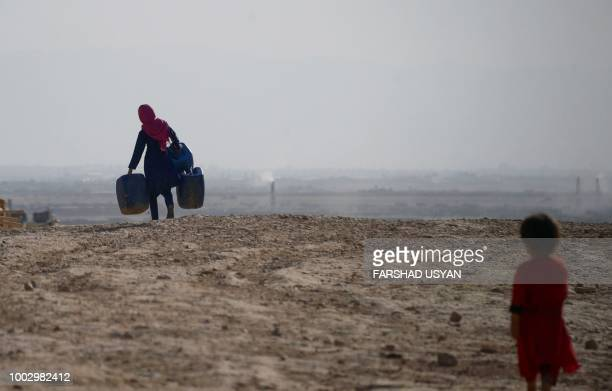In this photograph on July 19 an Afghan girl carries empty containers to collect water as a younger child looks on in Sakhi village on the outskirts...