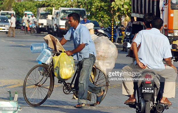 JAYASINGHE 'MALDIVESECONOMYBANGLADESHLABOURWASTE' In this photograph taken 20 October 2007 a Bangladeshi man pushes a bicycle loaded with bags of...