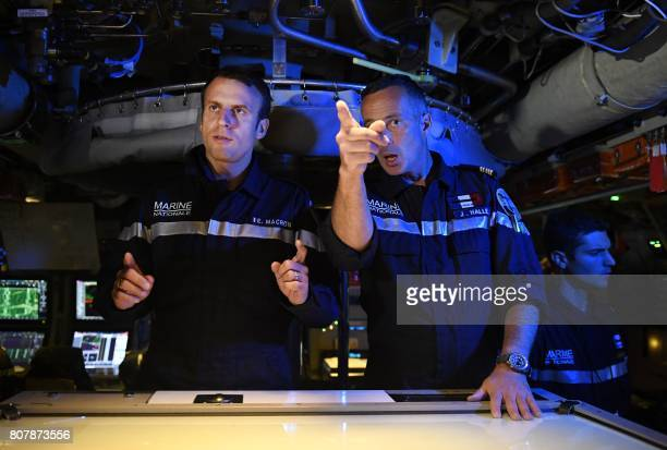 In this photograph taken at sea on July 4 French president Emmanuel Macron listens as Captain Jerome Halle commanding officer of the submarine 'Le...
