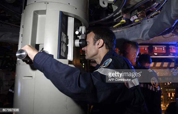 In this photograph taken at sea on July 4 French president Emmanuel Macron looks through the periscope of submarine 'Le Terrible' during a visit to...
