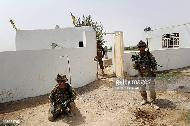 In this photograph taken August 10 An Afghan and US soldiers from Battle Company, 1-32 Infantry Battalion, 3rd Brigade Combat Team and Afghan...