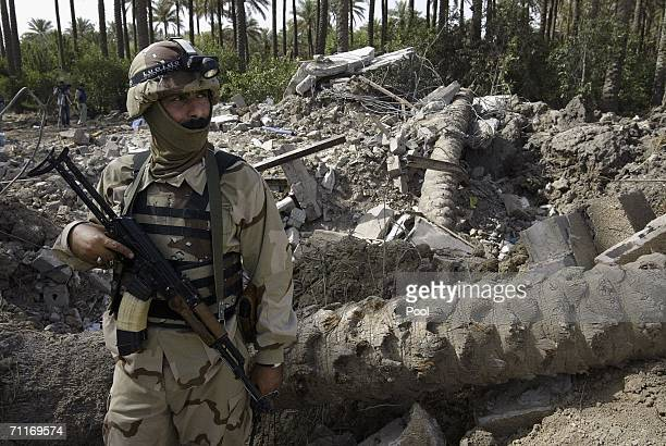 In this photograph taken during a US army media trip an Iraqi soldier guards the scene of the recent air strike against militant leader Abu Musab...