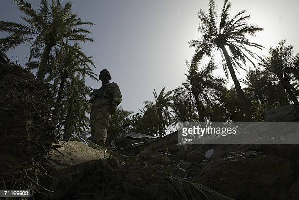 In this photograph taken during a US army media trip an Iraqi soldier looks down into a crater at the scene of the recent air strike against militant...