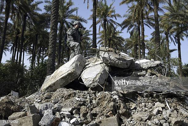 In this photograph taken during a US army media trip United States Army 4th Infantry Division soldier takes pictures of the scene of the recent air...