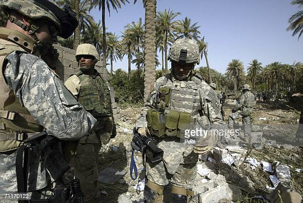 In this photograph taken during a US army media trip United States Army 4th Infantry Division soldiers look at destroyed Iraqi money at the scene of...