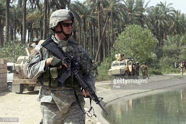 In this photograph taken during a US army media trip US Army 4th Infantry Division soldier guards a canal near the scene of the recent air strike...