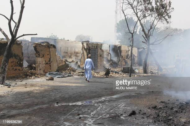In this photograph taken in Auno on February 10 a man walking past shops burnt down by suspected members of the Islamic State West Africa Province...