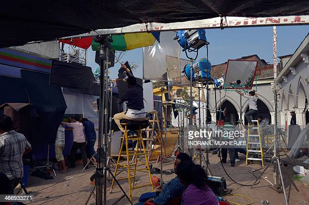 In this photograph taken January 21 Indian film crew work during a shoot at an outdoor studio set during a Bollywood Tourism package tour in Mumbai....
