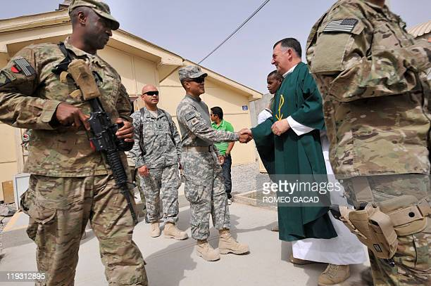 In this photograph taken July 17 Roman Catholic priest Fintan Kilmurray greets US soldiers after officiating a Sunday mass service and providing...