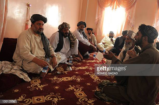 In this photograph taken July 27 Arghandab District Governor Haji Shah Mohamad listens to village elders during consultations in Arghandab district...