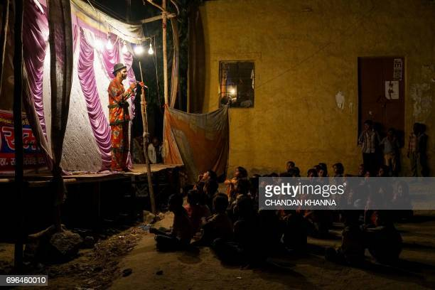 In this photograph taken June 15 Indian artists perform as people watch a 'Ramleela' folk play in Jaitaran some 80 km north of Jodhpur in the...