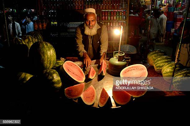 In this photograph taken late May 30 an Afghan street vendor prepares watermelons for customers at his roadside stall in Jalalabad. / AFP / NOORULLAH...