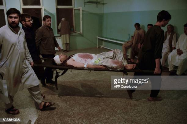 In this photograph taken late on August 1 Afghan men carry a wounded victim on a stretcher at a hospital following a suicide attack on a mosque in...