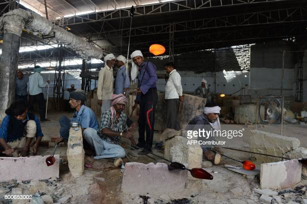 In this photograph taken on April 12 an Indian worker carries molten glass used to make bangles at a factory in Firozabad The ancient glass quarter...