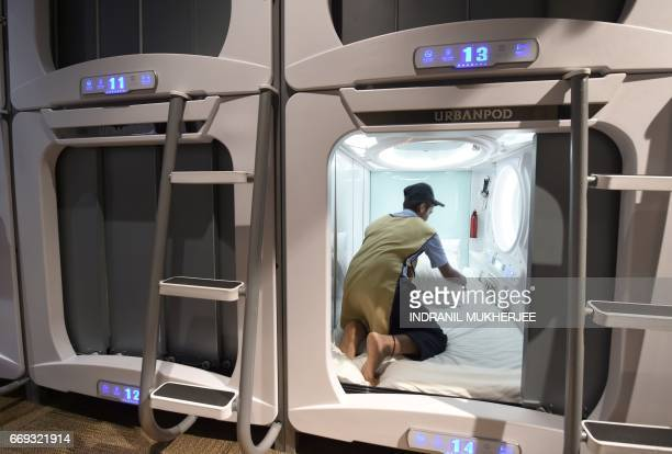 In this photograph taken on April 14 an Indian member of housekeeping staff cleans a pod at the Urbanpod hotel in Mumbai Mumbai's Urbanpod capsule...