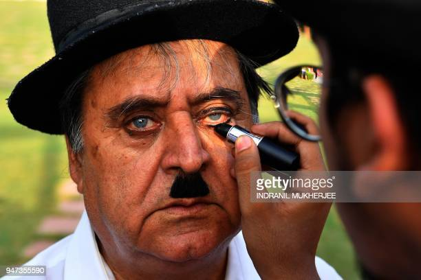 In this photograph taken on April 16 2018 Talin Mavani a Charlie Chaplin impersonator helps apply makeup for his grandfather Ashok Aswani founder of...