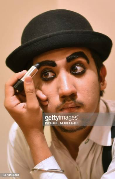 In this photograph taken on April 16 2018 Talin Mavani a Charlie Chaplin impersonator applies makeup before an event commemorating the legendary...