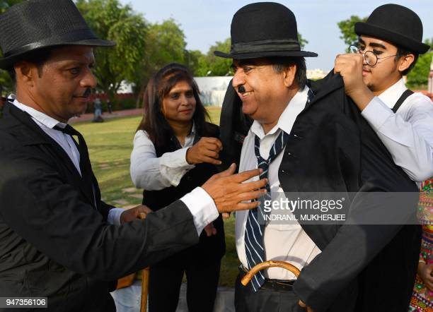 In this photograph taken on April 16 2018 Talin Mavani a Charlie Chaplin impersonator helps his grandfather Ashok Aswani founder of the Charlie...