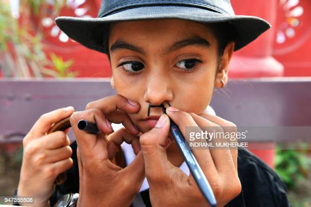 In this photograph taken on April 16 a young Charlie Chaplin impersonator is helped with makeup during an event commemorating the legendary actor's...