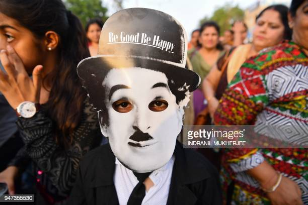 In this photograph taken on April 16 a young Charlie Chaplin impersonator wearing a mask with the face of the actor poses for a picture during an...