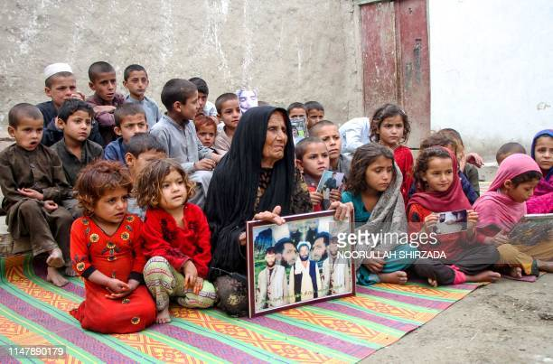 In this photograph taken on April 16 Afghan woman Niaz Bibi and her orphaned grandchildren sit at their home as she holds a framed photograph of her...