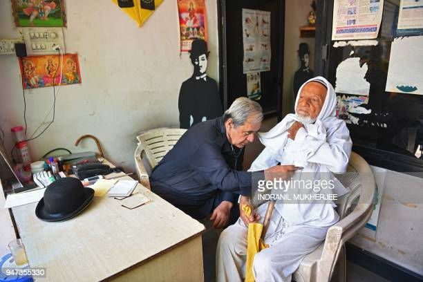 In this photograph taken on April 16 Ashok Aswani an ayurvedic doctor and founder of the Charlie Circle fan club checks a patient at his dispensary...