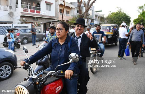 In this photograph taken on April 16 Ashok Aswani an ayurvedic doctor and founder of the Charlie Circle fan club waves to bystanders as his daughter...