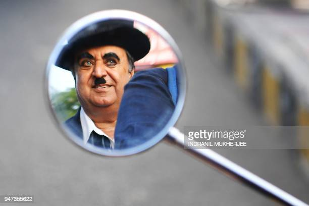 In this photograph taken on April 16 Ashok Aswani an ayurvedic doctor and founder of the Charlie Circle fan club is reflected in a mirror as his...