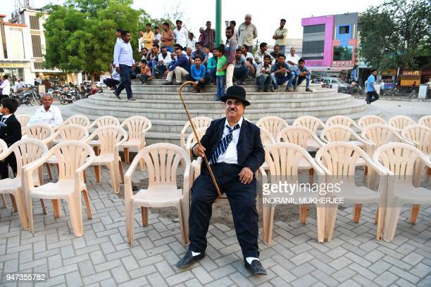 In this photograph taken on April 16 Ashok Aswani founder of the Charlie Circle fan club waits during an event commemorating the legendary actor...