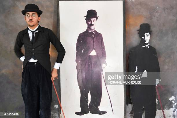 In this photograph taken on April 16 Talin Mavani a Charlie Chaplin impersonator checks his appearance in a mirror as he stands next to images of the...