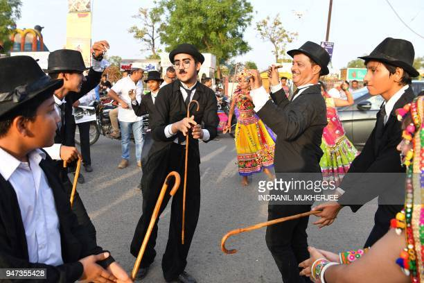 In this photograph taken on April 16 Talin Mavani a Charlie Chaplin impersonator breaks into a jig with other impersonators during an event...