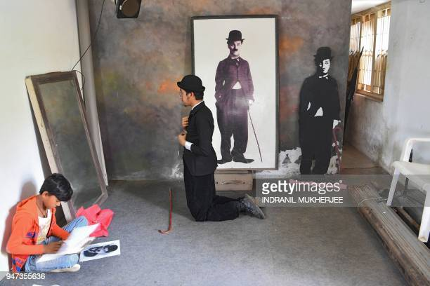 In this photograph taken on April 16 Talin Mavani a Charlie Chaplin impersonator checks his appearance in a mirror as a student takes part in a...